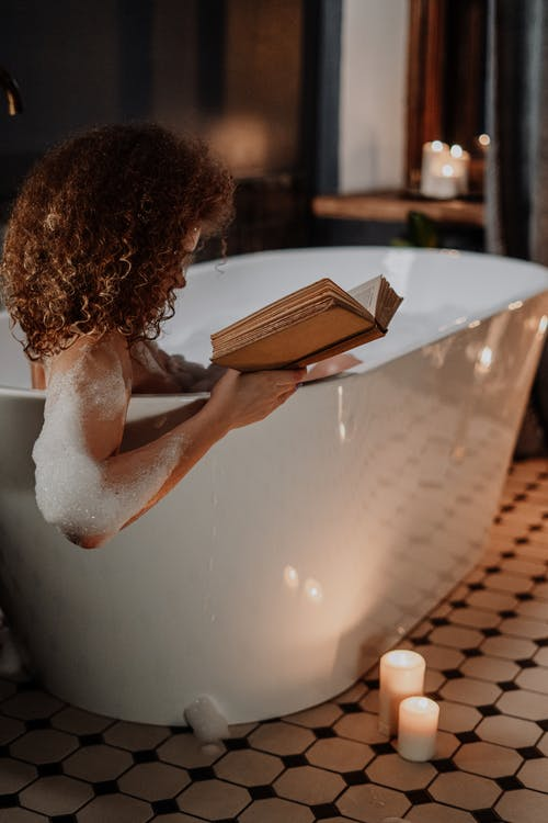 Woman in White Bath Tub Reading Book