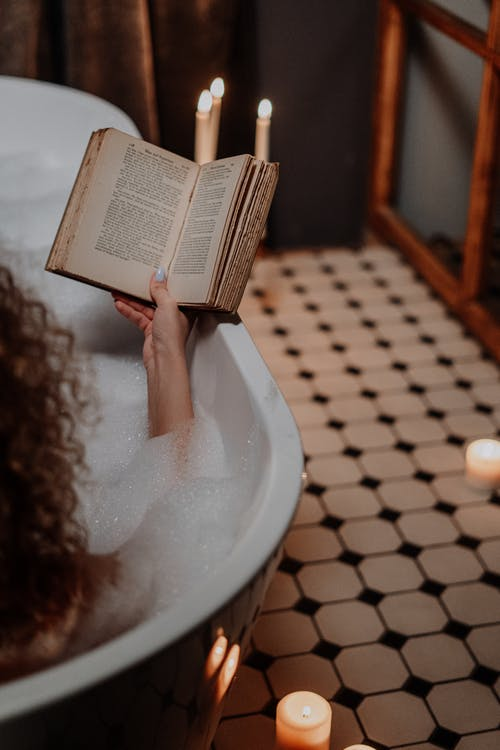 Person Reading Book in Bathtub