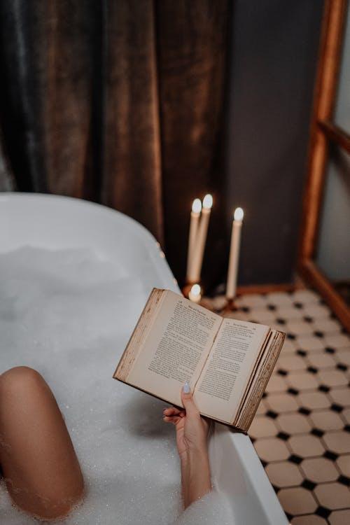 Person Reading Book on White Bathtub