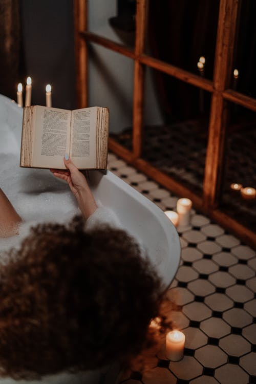 Person Reading Book on Bathtub