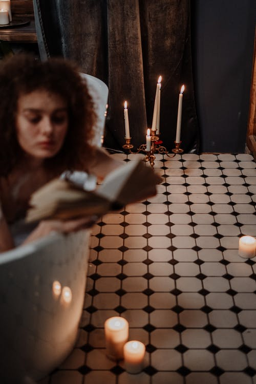 Woman Holding Lighted Candle in Front of Lighted Candles