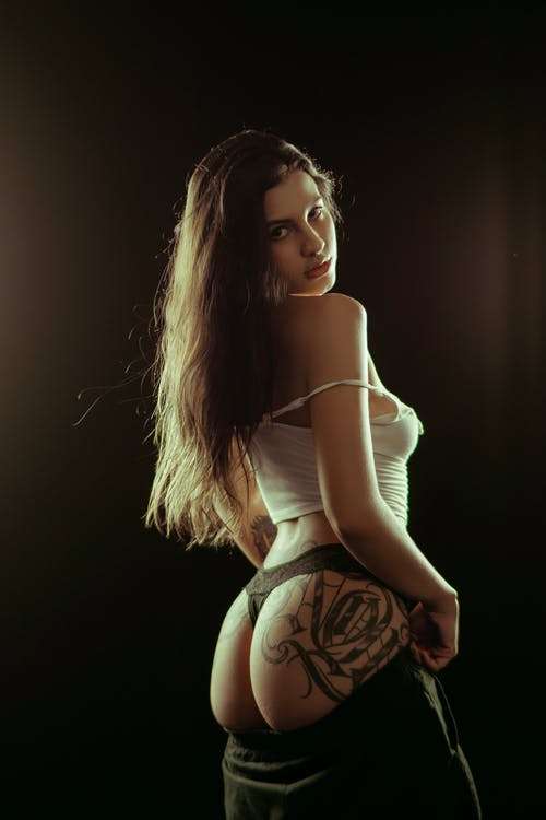 Back view of seductive young female showing buttocks with tattoo while standing against black background