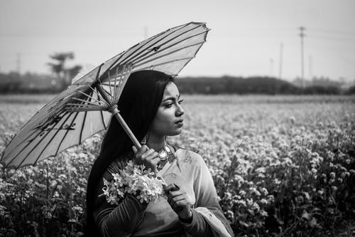 Ethnic woman with umbrella standing in blooming field