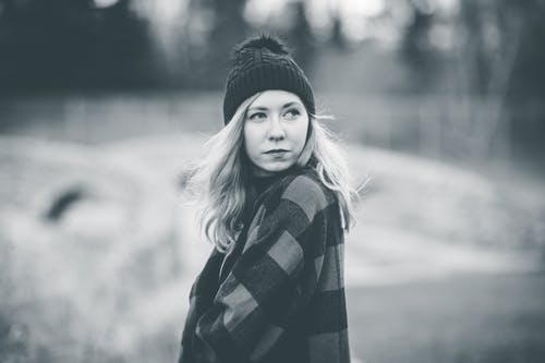 Calm woman in warm clothes in park