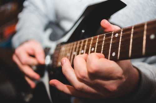 Selective focus of crop unrecognizable male musician playing electric guitar during music lesson