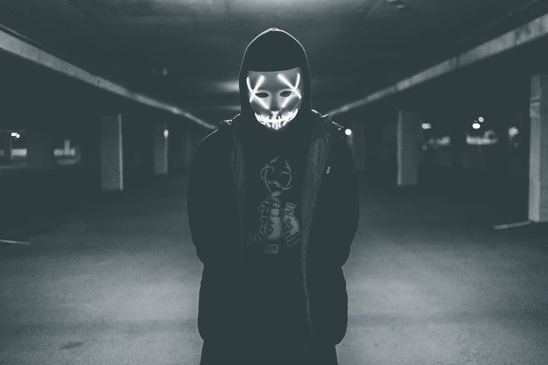 Man wearing hood and mask with neon lights
