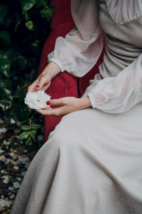 Woman in White Dress Holding White Rose