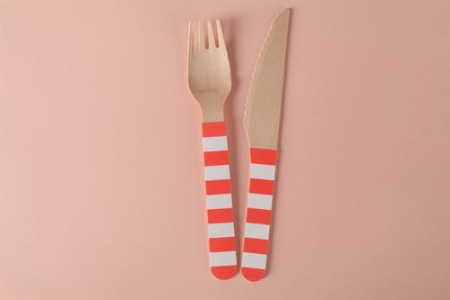 Close-Up Shot of Wooden Fork and Knife on a Pink Surface