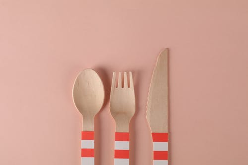 Close-Up Shot of Wooden Utensils on a Pink Surface