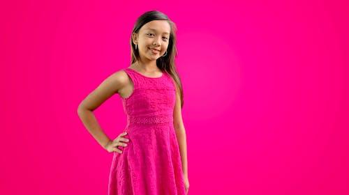Foto stok gratis berwarna merah muda, gadis muda, gaun merah muda, latar belakang merah jambu