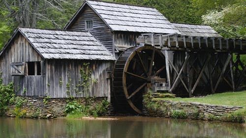 Gray Wooden House With Water Mill Surrounded by Trees