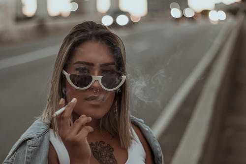 Young beautiful woman in sunglasses smoking on street