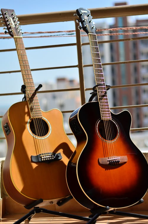View of beige and black brown new acoustic guitars on supports leaned to fence in sunlight