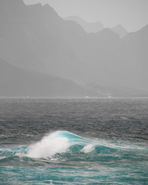 Ocean with foamy waves near powerful mountains
