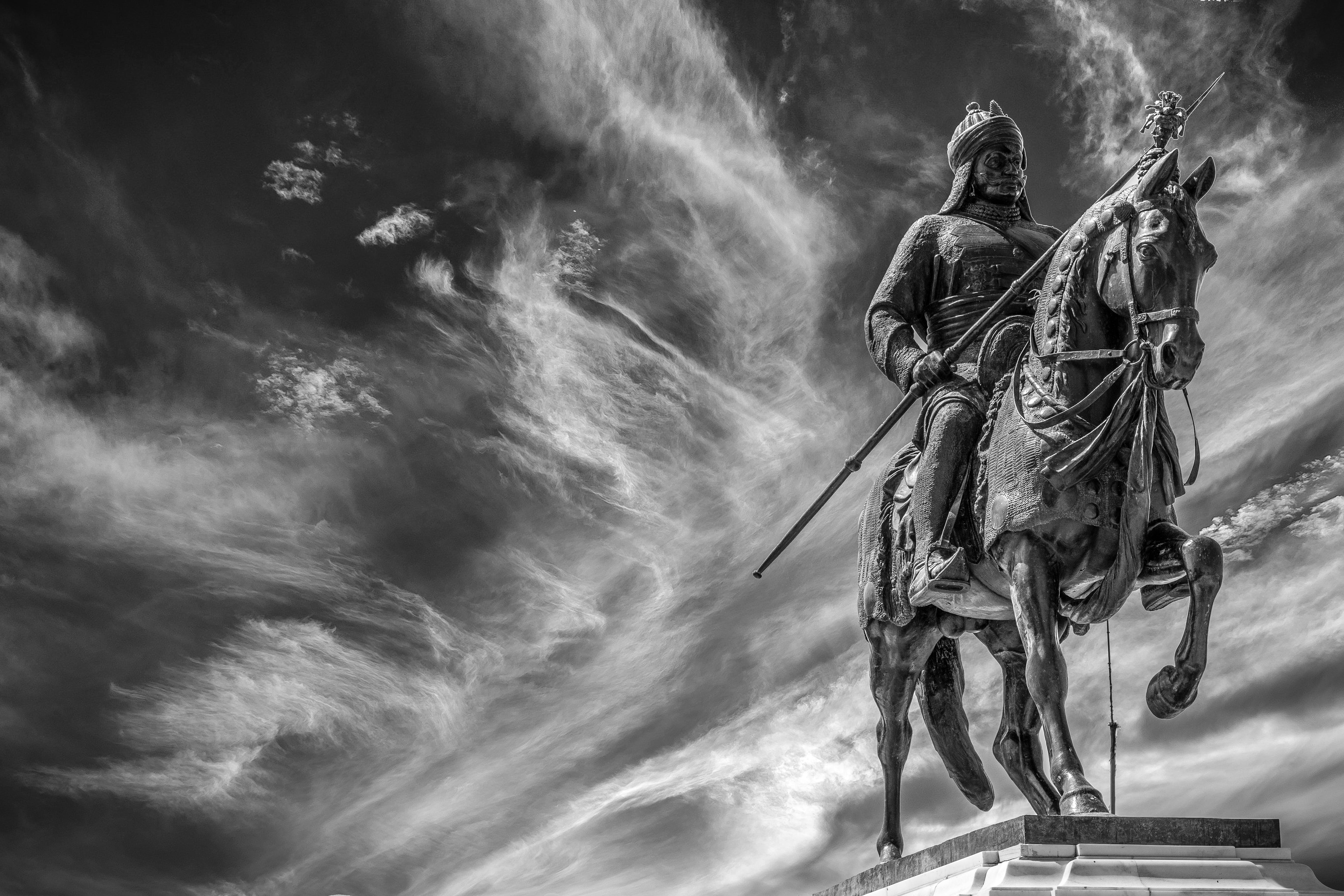 Gray Scale Photography of Man Riding Horse While Holding Spear