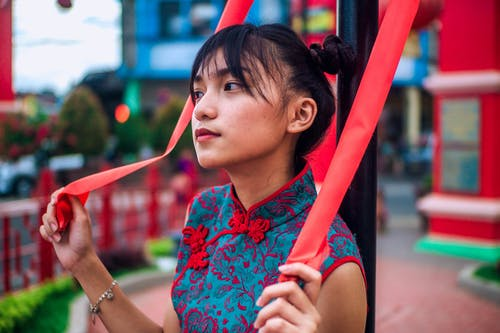 Pensive young ethnic lady resting in colorful park
