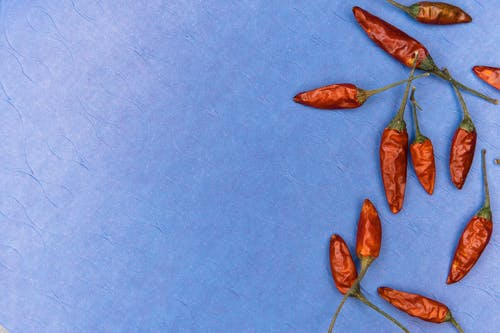 Close-Up Shot of Red Chili Peppers on a Blue Surface