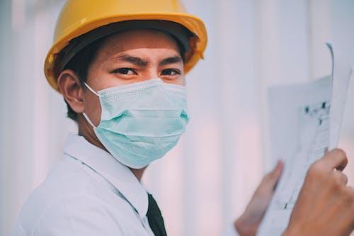 Man Wearing a Mask Holding a Blueprint
