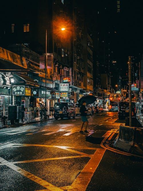 Unrecognizable man walking on crosswalk at night in rain