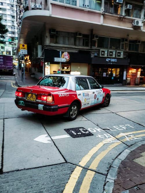 Retro red and white taxi car turning on narrow crossroad near typical building of city