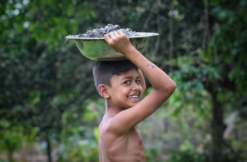 Happy Indian boy carrying metal bowl on head