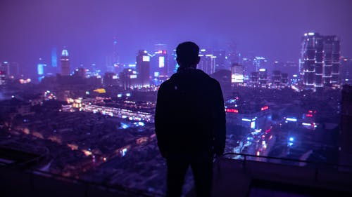Man in Black Jacket Standing on Top of Building during Night Time