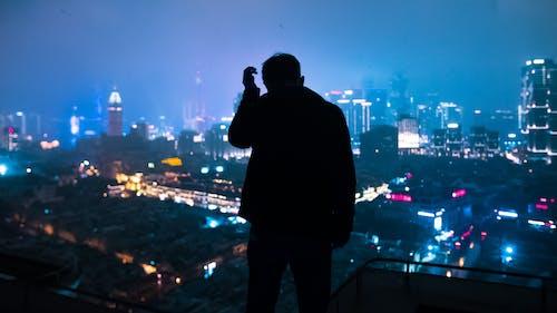 Man in Black Jacket Taking Photo of City during Night Time