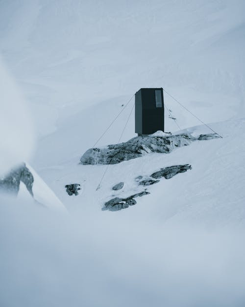 Expedition booth placed on stone on snowy mountain slope
