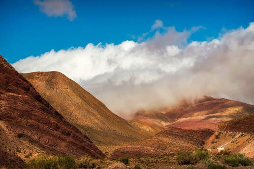Rainbow mountains under white clouds on sunny day