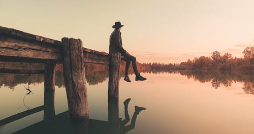 Silhouette of Man Sitting on Wood Log in Water during Sunset