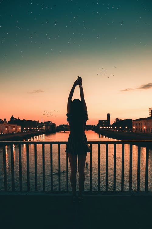 Silhouette of Woman Standing on Bridge during Sunset