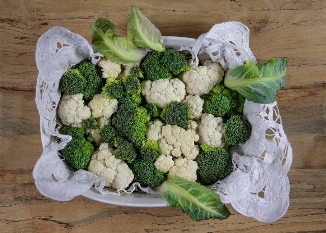 Green and White Broccoli on White Textile