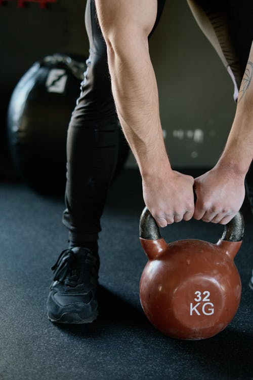 Person Holding Red Kettlebell