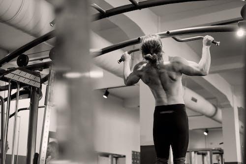 Topless Man Exercising at a Gym