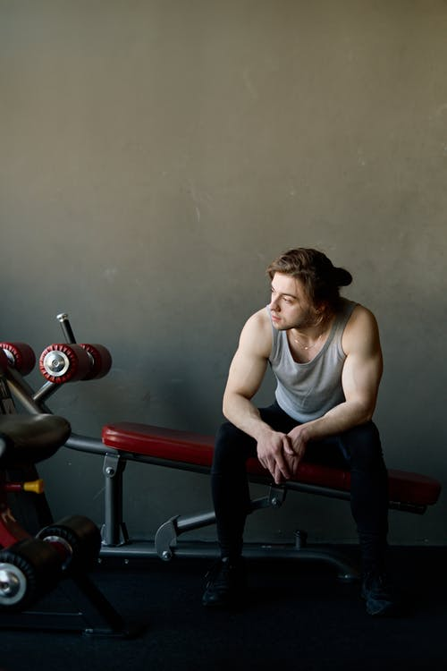 Man Sitting on Black and Red Exercise Equipment