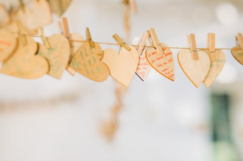 Creative rustic garland with timber hears hanging on rope with clothespins on blurred background