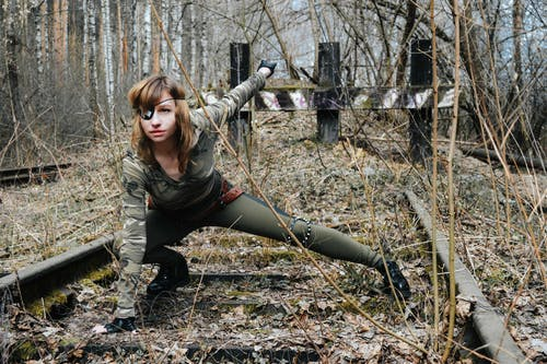 Military woman in camouflage clothes in woods