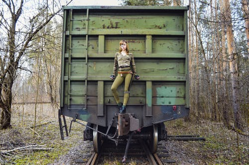 Confident female in camouflage clothes on military train