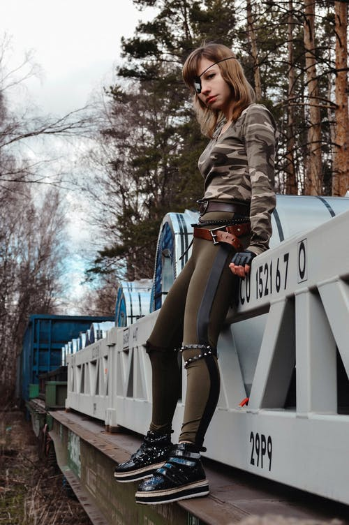 Confident military woman on train in woods