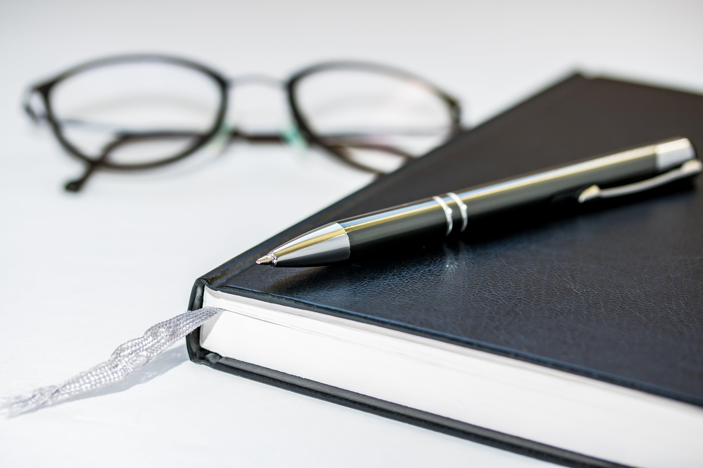 Foto stok gratis berbayang, buku agenda, kacamata untuk membaca, pena