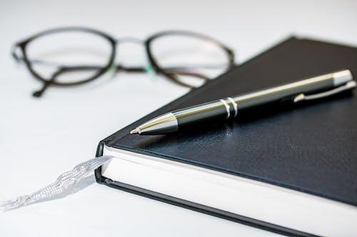 Fotos de stock gratuitas de bolígrafo, cuaderno, efecto desenfocado, gafas de lectura