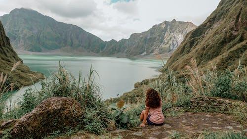 Woman in Black Tank Top Sitting on Brown Grass Near Lake