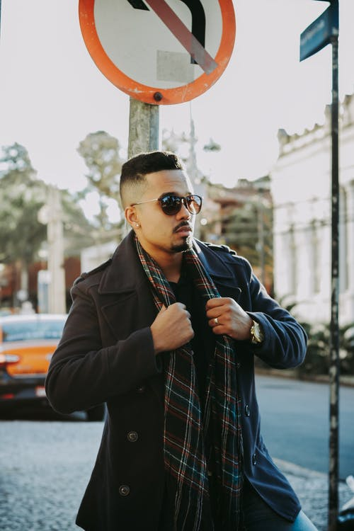 Cool young man in coat and sunglasses on street