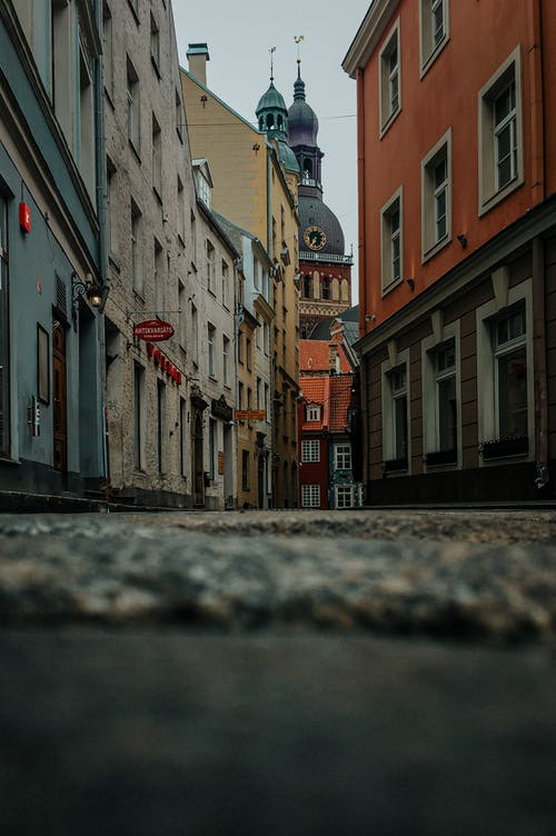 Ground level of empty narrow paved street between aged buildings leading to historical Cathedral Church of Saint Mary located in Riga
