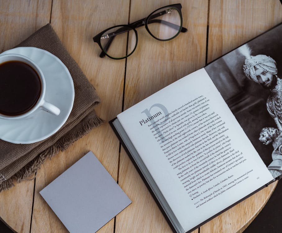 Opened book and sticky note placed on table with coffee cup and eyeglasses