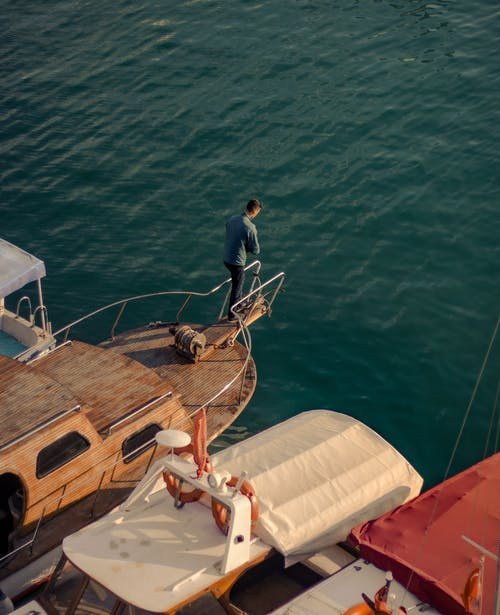Man in Blue Long Sleeve Shirt and White Pants Standing on Brown Wooden Boat