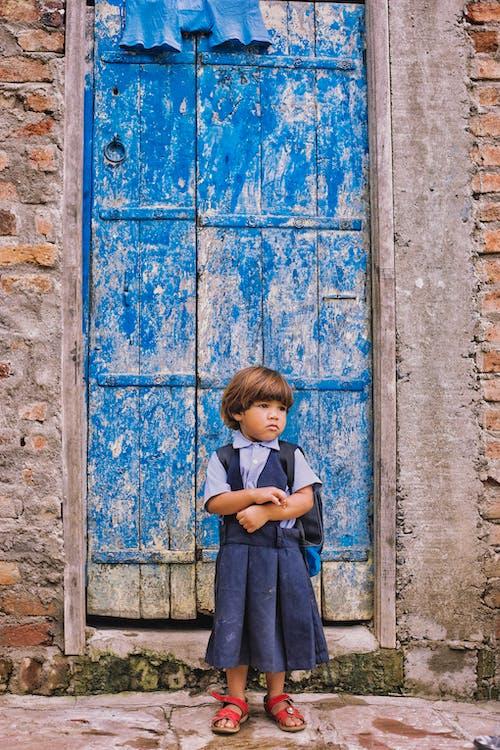 A Sad Girl in School Uniform Standing in front of a Blue Wooden Door