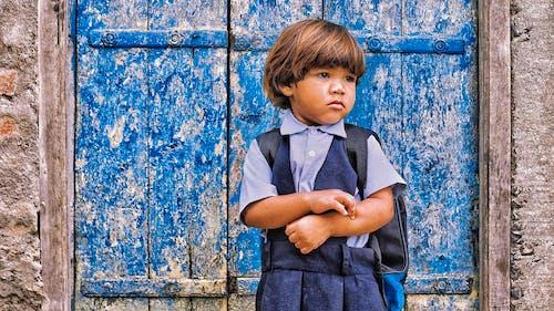 Close-Up Shot of a Girl in School Uniform Standing in front of a Blue Wooden Door