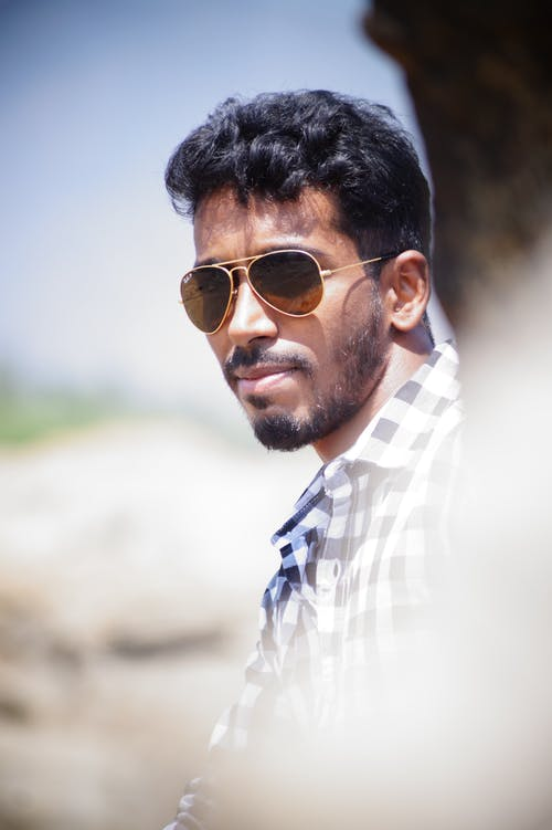 Side view of serious bearded Indian man wearing trendy sunglasses and checkered shirt against blurred background of nature
