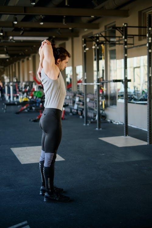 Man Stretching at a Gym
